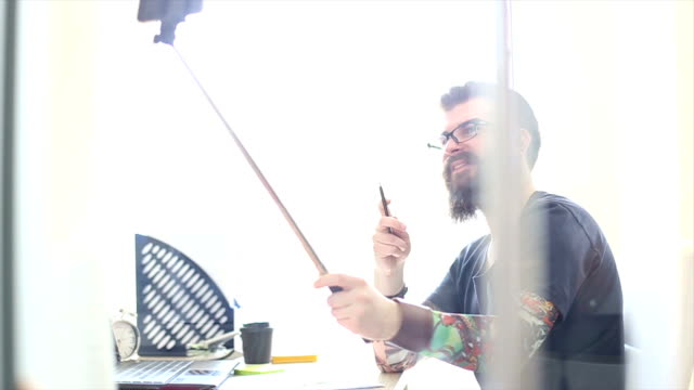 Tattooed hipster beard is having fun in the office video