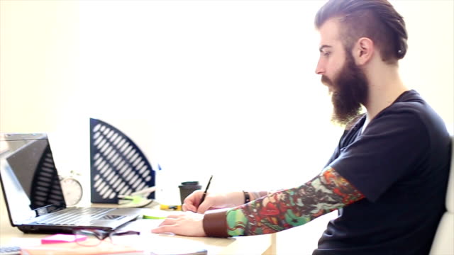 Tattooed hipster beard working in the office video