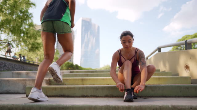 Tattooed Latin female athlete tying shoelaces on outdoor steps