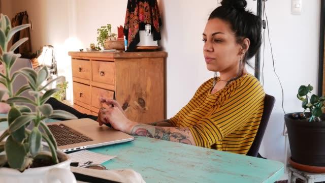 tattooed latina freelancer working from home or using e-learning app - tatuaż filmów i materiałów b-roll