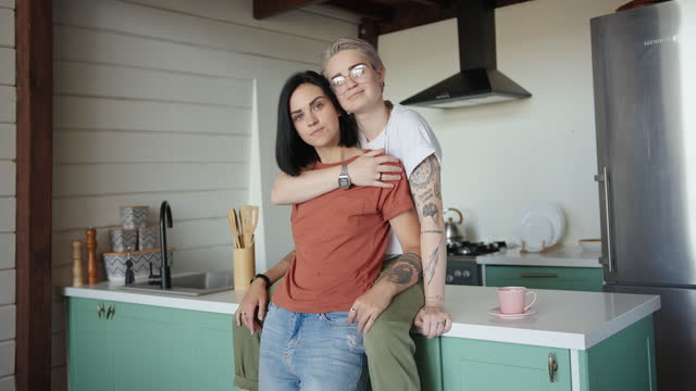 Tattooed lesbian with fair hair and glasses hugs brunette