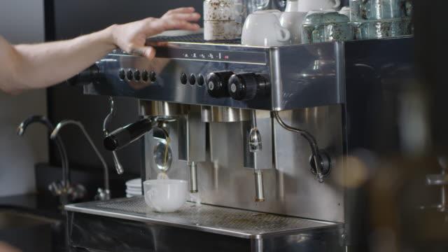 tattooed male barista making americano on coffee machine - tap water filmów i materiałów b-roll