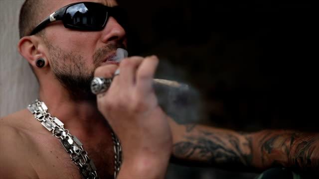 stockvideo's en b-roll-footage met tattooed man roken van een joint - ring juweel