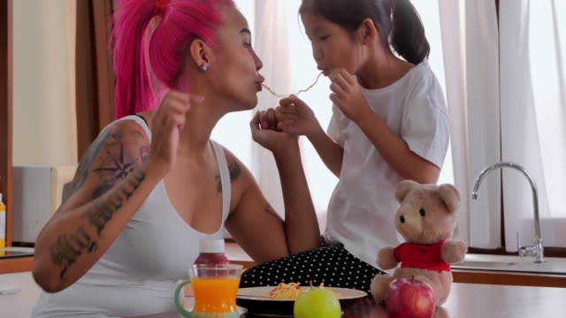 Tattooed mother at home with daughter eating spaghetti and spending time with her cute baby at home.Day in the Life of a Family - vídeo