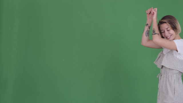 tattooed woman having fun dancing over green background - comparsa video stock e b–roll