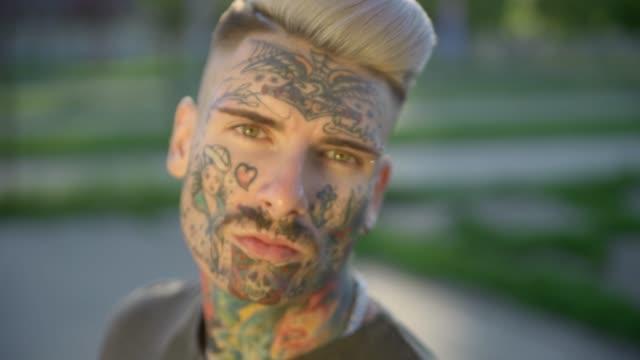 tattooed young man outdoors - tatuaż filmów i materiałów b-roll