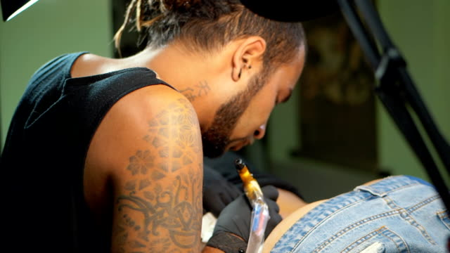 Tattooist does tattoo a client with machine close up. Process getting tattoo in a parlor. Body tattooing process. Man with dreadlocks working on female body part under lamp. Slow motion video