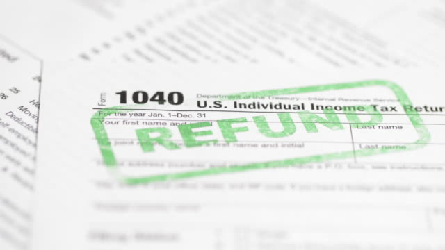"IRS Tax form 1040 - 4K A 4K resolution stock video of a IRS 1040 tax form. Showing the words ""Refund"" in the form of a green ink stamp taxes stock videos & royalty-free footage"