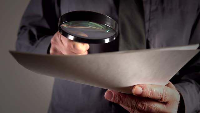 steuerinspektor untersucht finanzdokumente durch magierglas - lupe stock-videos und b-roll-filmmaterial