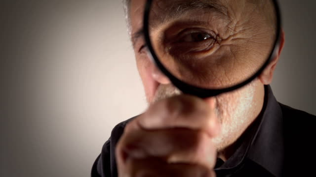 tax inspector looking through magnifying glass - curiosità video stock e b–roll