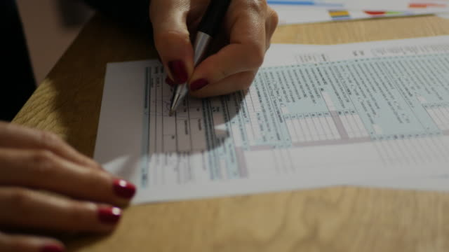 Taxation in USA and Tax Form 1040 - businesswoman filling out the document