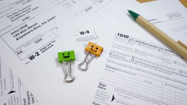 Taxes Form 1040, W-2 and W-9 with Smiles Binder Clips and Pen