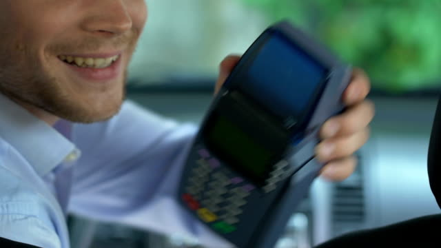 vídeos de stock e filmes b-roll de taxi driver giving payment terminal to client, easy cashless transfer, services - paying with card contactless