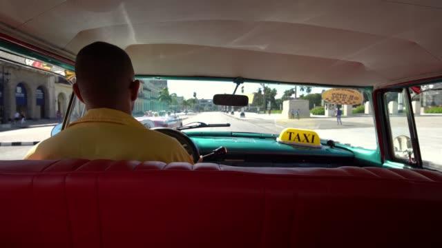 taxifahrer in klassische amerikanische 1950 oldtimer fahrt auf der berühmten straße im alten viertel der havanna, kuba - havanna stock-videos und b-roll-filmmaterial