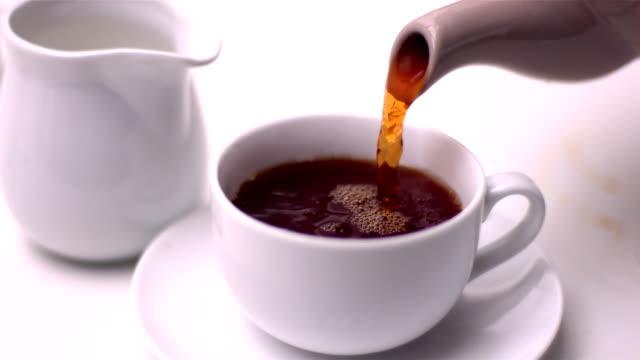 tee wird eingeschenkt in tasse von teekanne - milchkrug stock-videos und b-roll-filmmaterial
