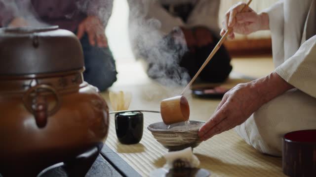 vidéos et rushes de cérémonie du thé hôte préparant le thé pendant que les invités mangent - culture japonaise