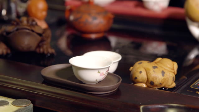 tea ceremony. master pours tea on white cups - teapot stock videos & royalty-free footage
