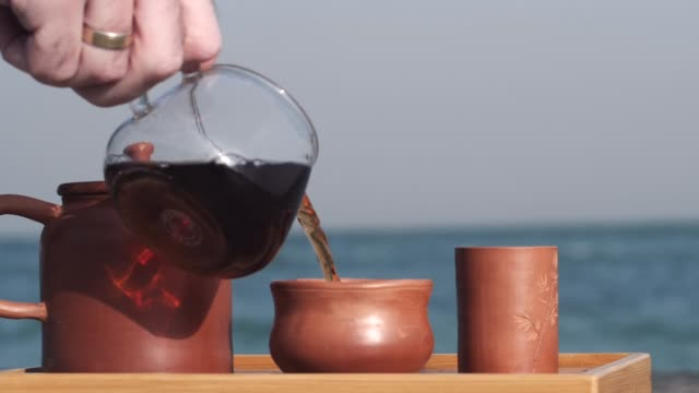 Cerimônia de Chá com Yixing Teapot. Chá no píer à beira-mar - vídeo