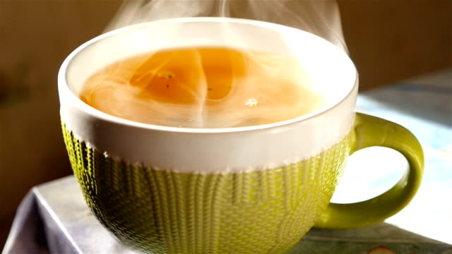 Tea in a large cup. Transparent steam. Slow motion video