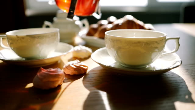 tea is poured into cups. Beautiful atmospheric steam. Sunday morning. Croissants and desserts. Video footage