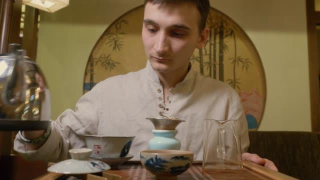 vídeos y material grabado en eventos de stock de maestro de té vertiendo agua caliente del hervidor a gaiwan para elaborar cerveza té en ceremonia - porcelana china