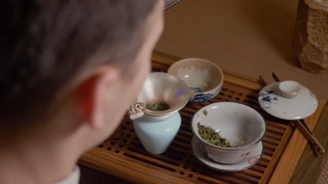 Tea master pours hot water from kettle to gaiwan. Steam from hot cup. Green tea