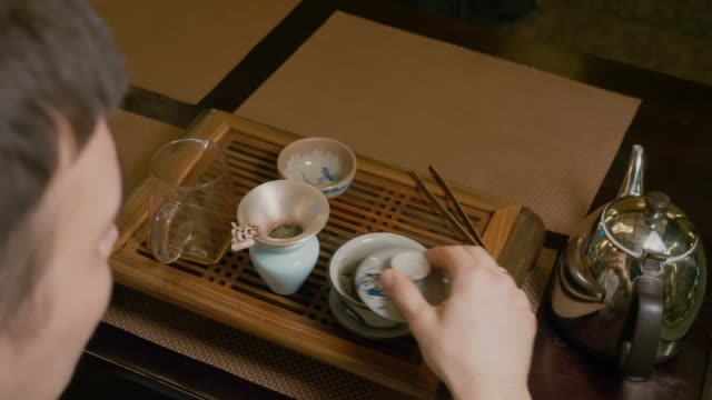 Tea master pours hot water from kettle to gaiwan with green tea at wooden table Tea master pouring hot water from kettle pitcher to gaiwan with green tea at wooden table. Man preparing chinese tea by to ancient traditional custom. Chinese tea ceremony. View from shoulders philosophy stock videos & royalty-free footage