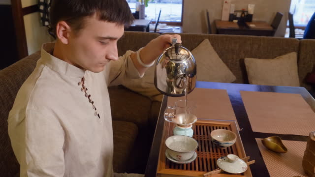 Tea master using hot water for warming tea bowl and fairness pitcher at ceremony
