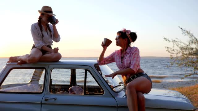 tea party of Beautiful girls to car hood on Embankment in sunset, girlfriends drinking Tea video