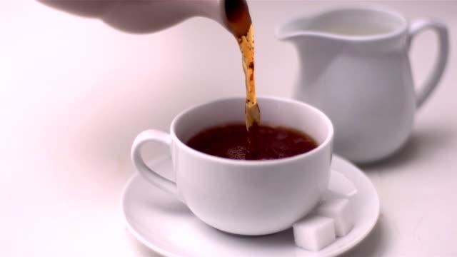 tee eingießen in teetasse - milchkrug stock-videos und b-roll-filmmaterial
