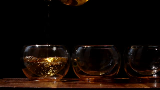 Tea pouring to tree glass on dark ground