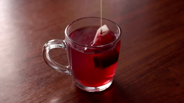 Teabag in the cup with hot water. Close-up of a glass mug with hot water and a bag of floral red tea, slow motion. A girl is brewing a bag of tea in a mug on a wooden background. boiled stock videos & royalty-free footage