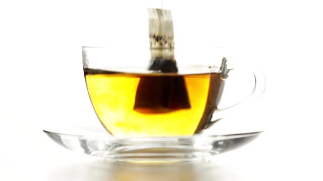 Teabag is dip into hot water Tea bag is dip into hot water. Water starts to change color slowly drenched stock videos & royalty-free footage