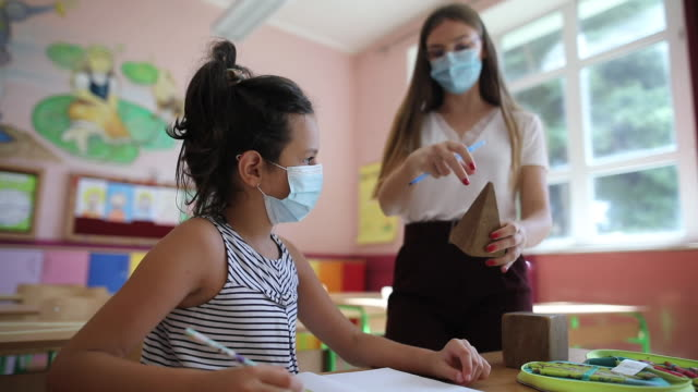 Teacher and girl with protective face masks on class during covid-19 pandemic