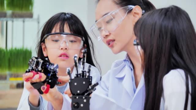 учитель и группа детей работает над полностью функциональной программируемой роботизированной рукой для проекта клуба школьной робототе� - манипулятор робота производственное оборудование стоковые видео и кадры b-roll