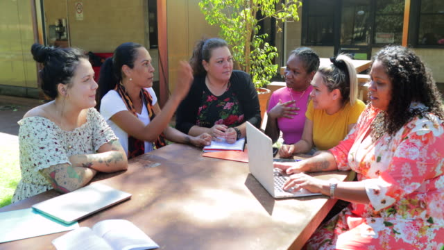 Teacher And Her Female Students Wide static shot of young aboriginal female students sitting with their tutor outdoors in the sun in Australia. minority groups stock videos & royalty-free footage