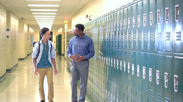 stockvideo's en b-roll-footage met leraar en middelbare schoolstudent die in gang loopt - afro amerikaanse etniciteit