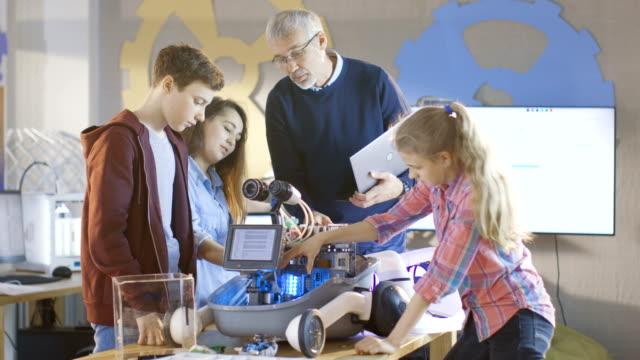 先生とその弟子たちは、プログラマブル ロボット学校科学のクラスのプロジェクトの LED 照明で動作します。 ビデオ