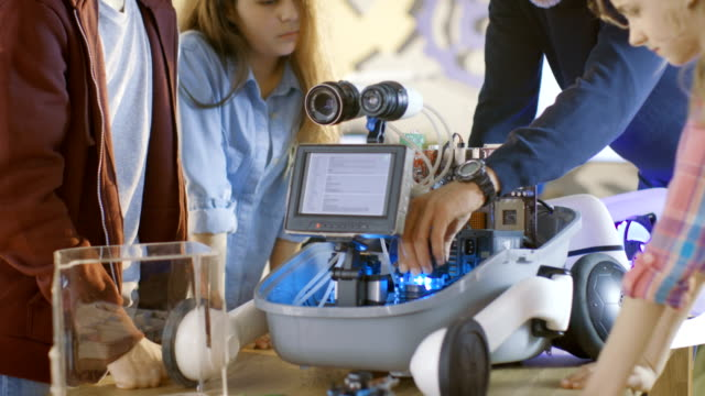 öğretmen ve öğrencileri okul bilim sınıf projesi için led aydınlatmalı programlı bir robot üzerinde çalışmak. - estonya stok videoları ve detay görüntü çekimi
