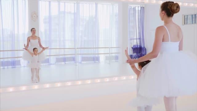 lehrer und kleines mädchen trainieren ballettschritte in der nähe des spiegels auf tanzkurs - mittelstufenlehrer stock-videos und b-roll-filmmaterial