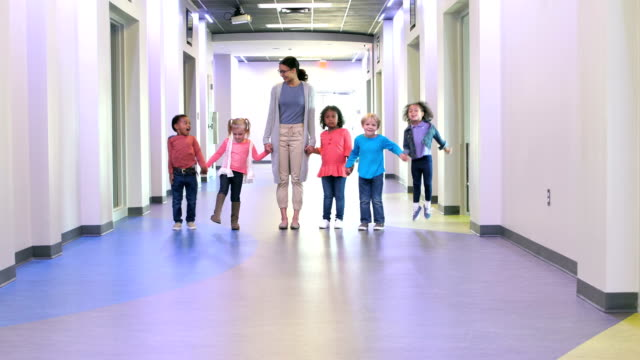 Teacher and preschool children holding hands in hallway A multi-ethnic group of five preschool children and their teacher standing side by side in a school hallway, holding hands. child care stock videos & royalty-free footage