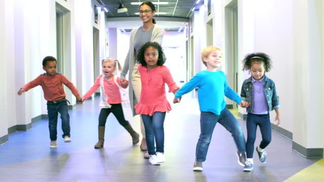 vídeos de stock, filmes e b-roll de professor e pré-escola as crianças de mãos dadas no corredor - professor de pré escola