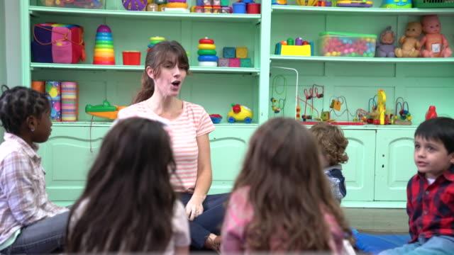 vídeos de stock, filmes e b-roll de professor e pré-escola crianças batendo palmas em sala de aula - professor de pré escola