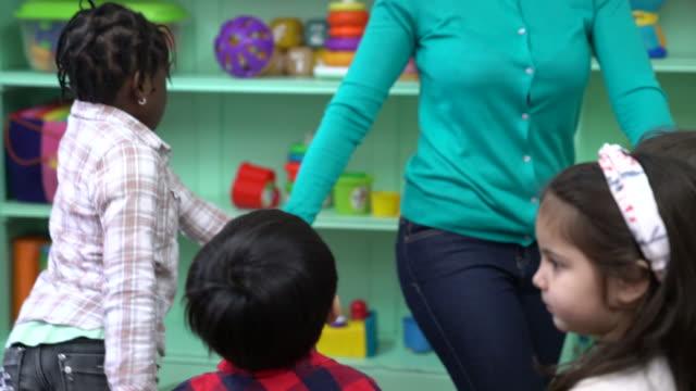 vídeos de stock, filmes e b-roll de professor e pré-escola crianças brincando no jardim de infância - professor de pré escola