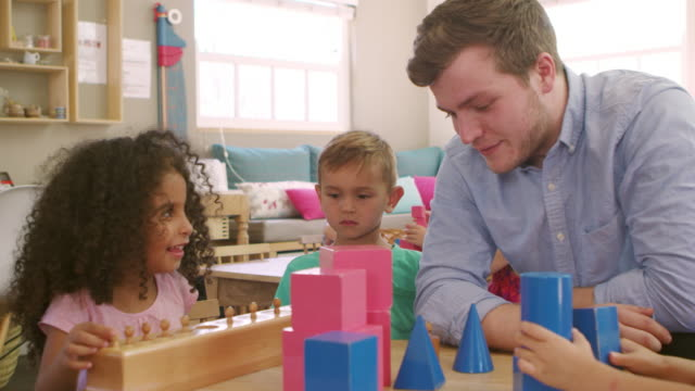 Teacher And Pupils Using Wooden Shapes In Montessori School video