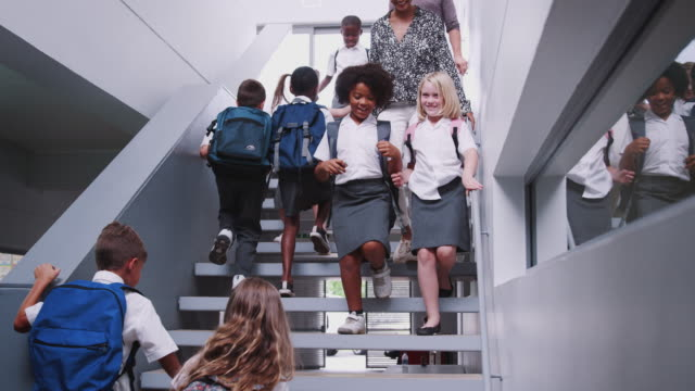 Teacher And Pupils Walking Down Stairs In Busy Elementary School Corridor Teachers and pupils wearing uniform walking down stairs of school building between lessons - shot in slow motion primary school stock videos & royalty-free footage