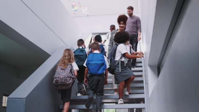 Teacher And Pupils Walking Down Stairs In Busy Elementary School Corridor