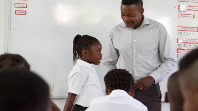 Teacher and schoolgirl in front of elementary school class video