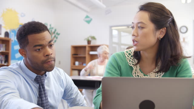 Teacher and student using laptop at an adult education class video