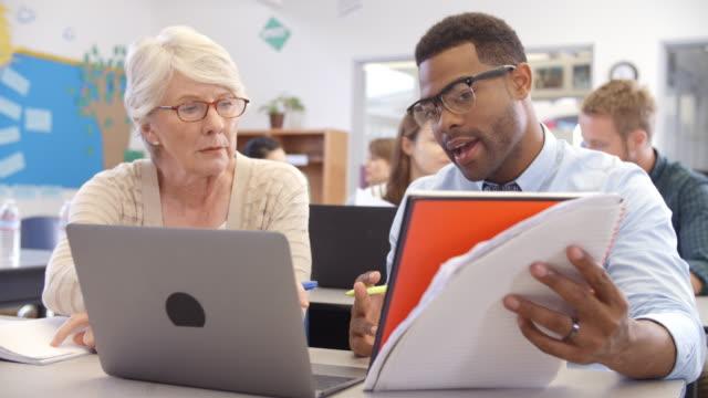 stockvideo's en b-roll-footage met leraar en student met behulp van laptop op een volwassenonderwijs klasse - student